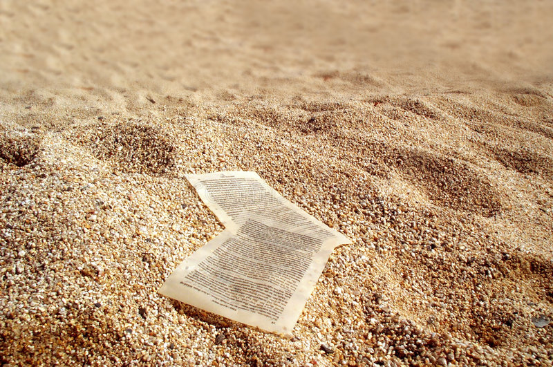Paper sheets on golden sands royalty free stock photo