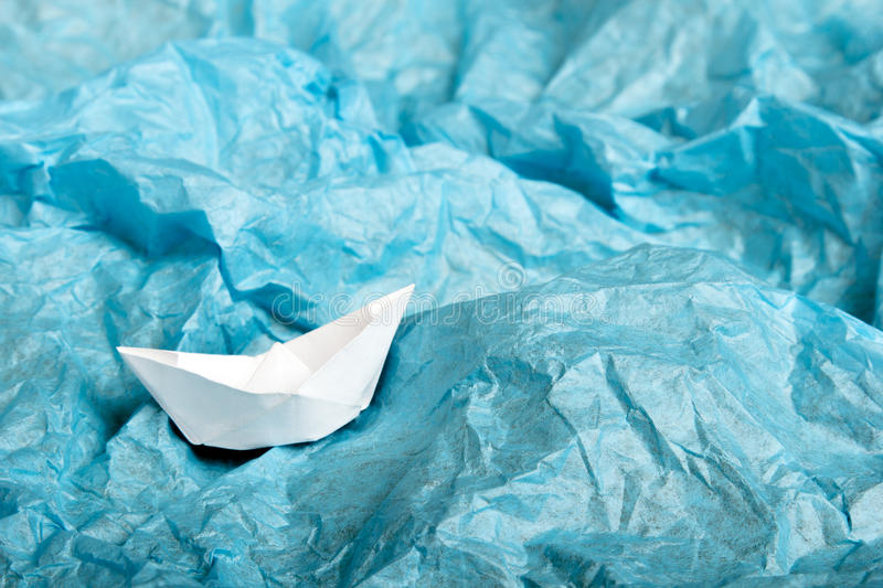Paper ship in blue tissue paper. Children`s idea of the ship at sea stock photos