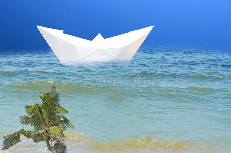 Paper ship in the sea. Symbolizing vacation with cruise ship. Blue sea in the background a blue sky. At sea, a big ship of paper. Symbolizing vacation with a stock images