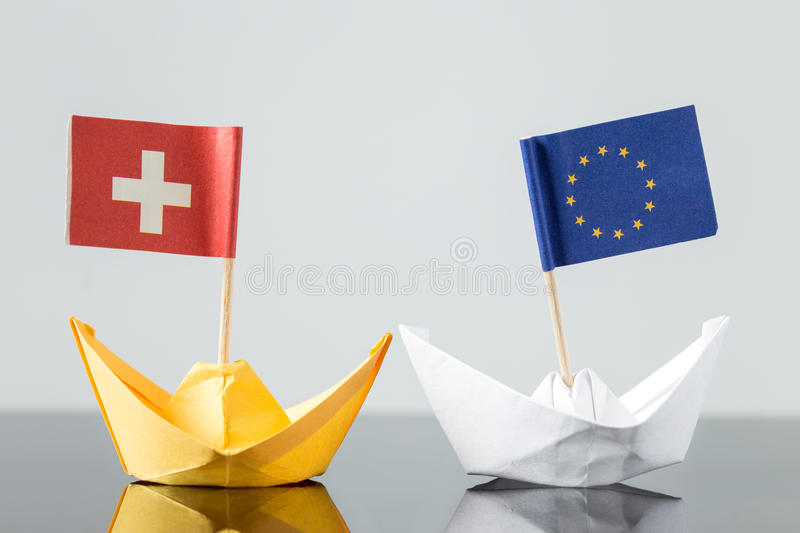 Paper ship with swiss and european flag. Concept shipment or free trade agreement and membership of eu, referendum stock photography