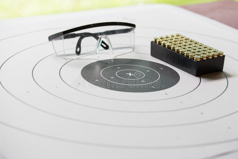 Paper shooting target with safety glasses and 9 mm bullet for sh royalty free stock photos
