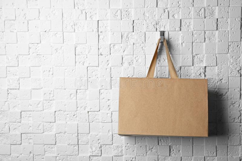 Paper shopping bag with comfortable handles hanging. On white wall. Mockup for design royalty free stock photo