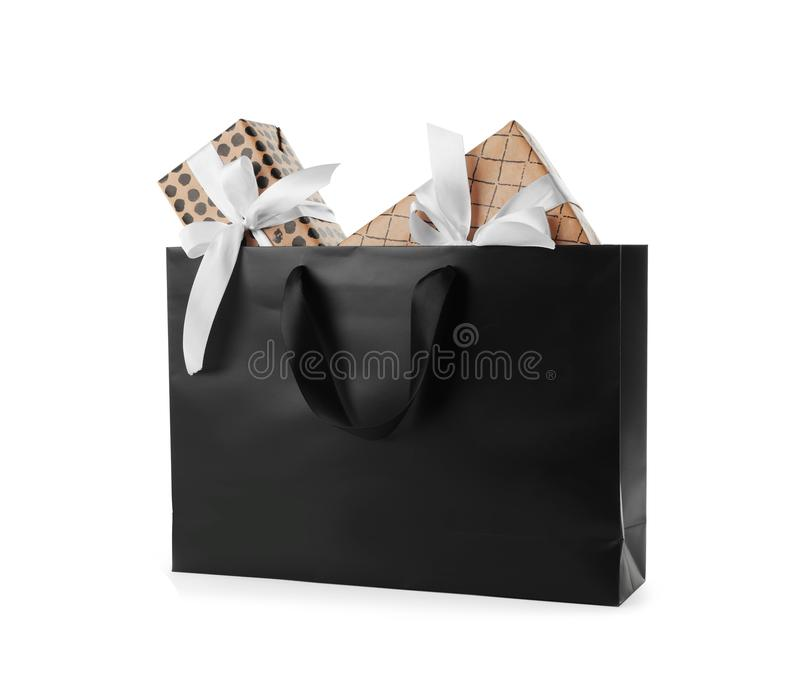 Paper shopping bag with handles full of gift boxes on white background. Mock up for design royalty free stock image