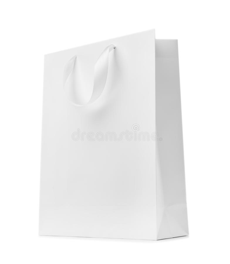 Paper shopping bag with ribbon handles on white background. royalty free stock images