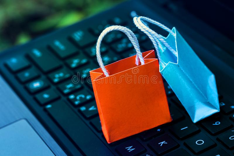 Paper shopping bags on a laptop keyboard. Ideas about online shopping addiction. someone who shops compulsively which appears as stock image
