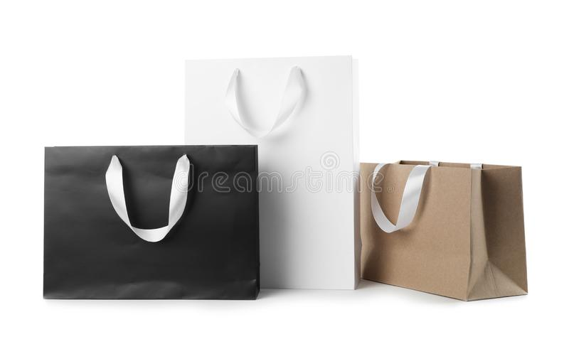 Paper shopping bags with ribbon handles on white background. Mockup for design royalty free stock photography