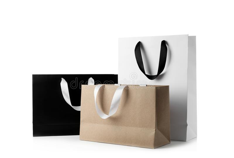 Paper shopping bags with ribbon handles on white background. stock images