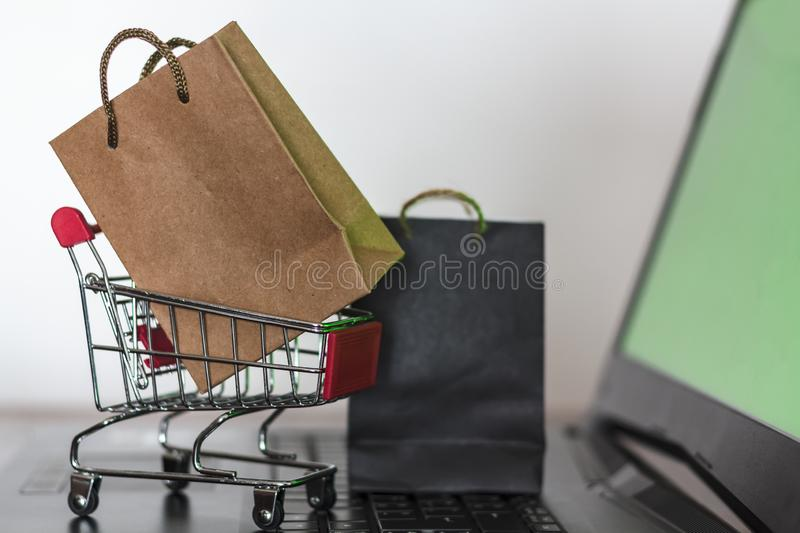 Paper shopping bags and shopping trolley on computer with green screen. Online Shopping and e-commerce concept stock photos