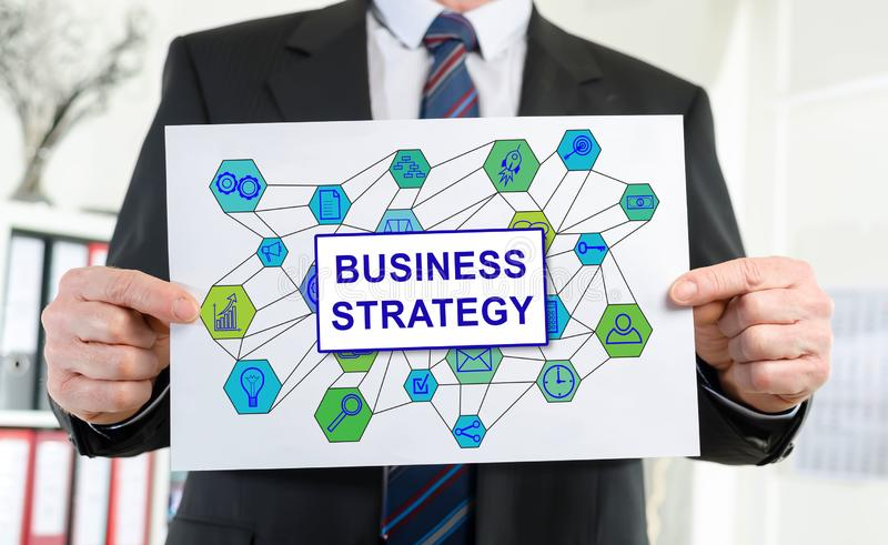 Business strategy concept shown by a businessman. Paper showing business strategy concept held by a businessman stock photo