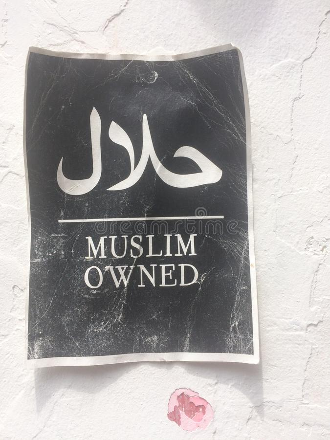 Paper sign with the text & x22;Muslim owned& x22; hanging on a wall on the Haji Lane in Singapore. Close up picture of a printed paper sign, with the text & x22 stock photography
