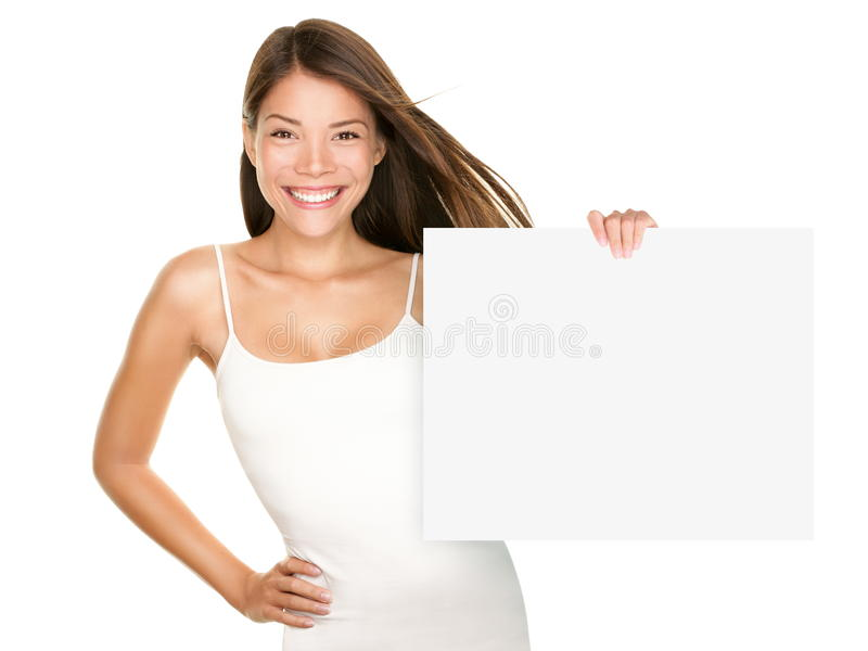Paper sign woman smiling. Cute lovely fresh girl advertising your product on blank white sign board. Asian Caucasian female model isolated on white background stock photography