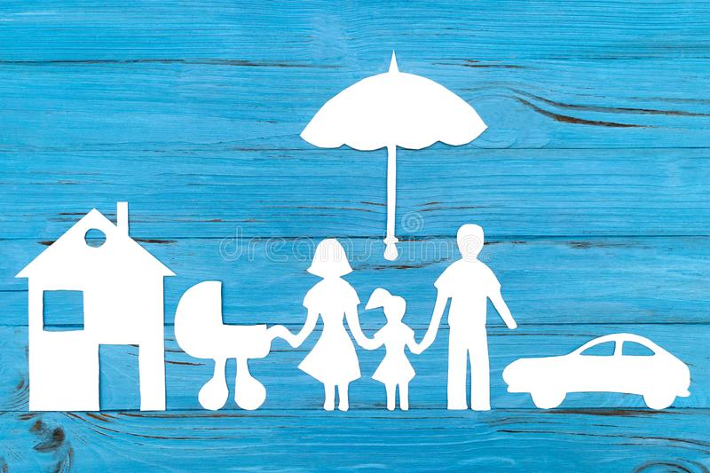 Paper silhouette of family with baby carriage under umbrella. Car and house on blue wooden background. Life insurance concept royalty free stock photos