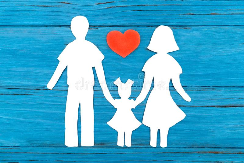 Paper silhouette of family with red heart. On blue wooden background. Concept of family love stock image