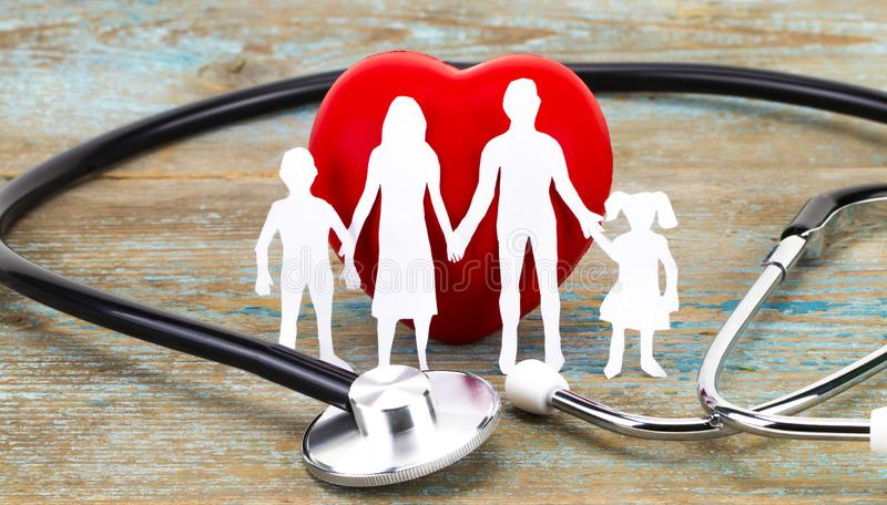 Paper silhouette of family, stethoscope and heart on wooden background. Health insurance concept.  stock image