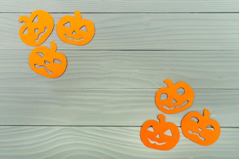 Paper silhouette of six different pumpkin. Top view of paper silhouette of six different pumpkin made of vertical frame on grey wooden background. Halloween royalty free stock images
