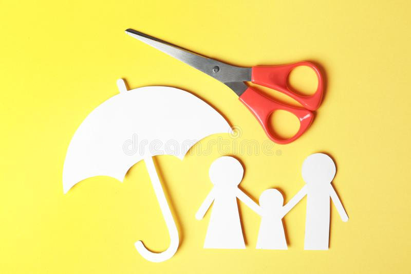 Paper silhouettes of family with umbrella and scissors on color background, flat lay. Life insurance stock photo