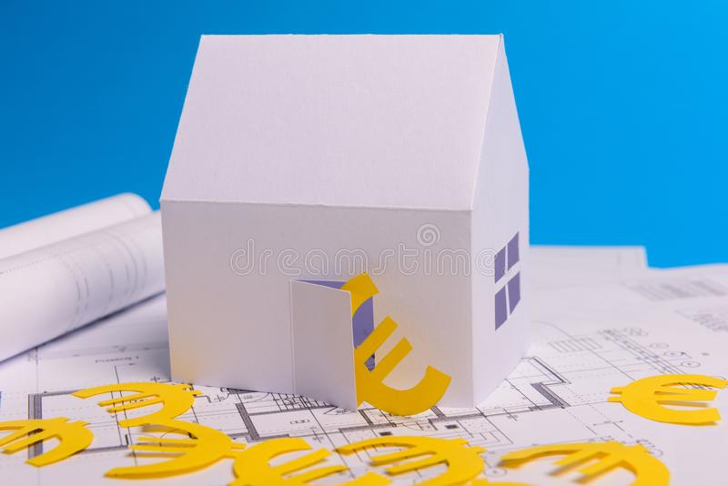 Paper skyscrapers , euro money, house projects plan and blueprints on blue background paper. Minimalistic and simple concept,. Style. Horizontal orientation royalty free stock photography