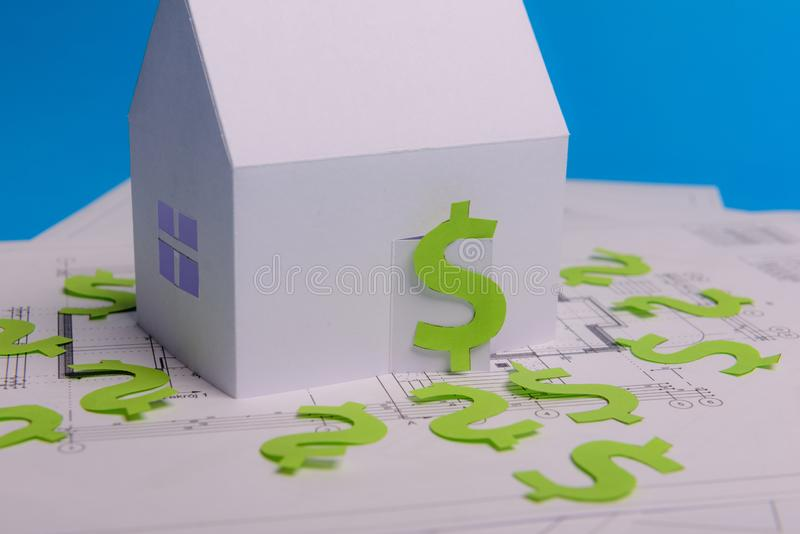 Paper skyscrapers , us dollar money, house projects plan and blueprints on blue background paper. Minimalistic and simple concept. Style. Horizontal stock photo