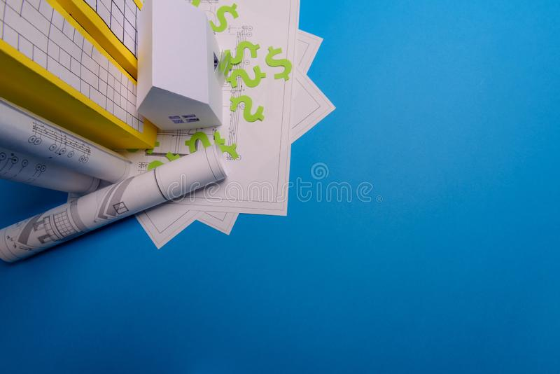 Paper skyscrapers , us dollar money, house projects plan and blueprints on blue background paper. Minimalistic and simple concept. Style. Horizontal royalty free stock photo