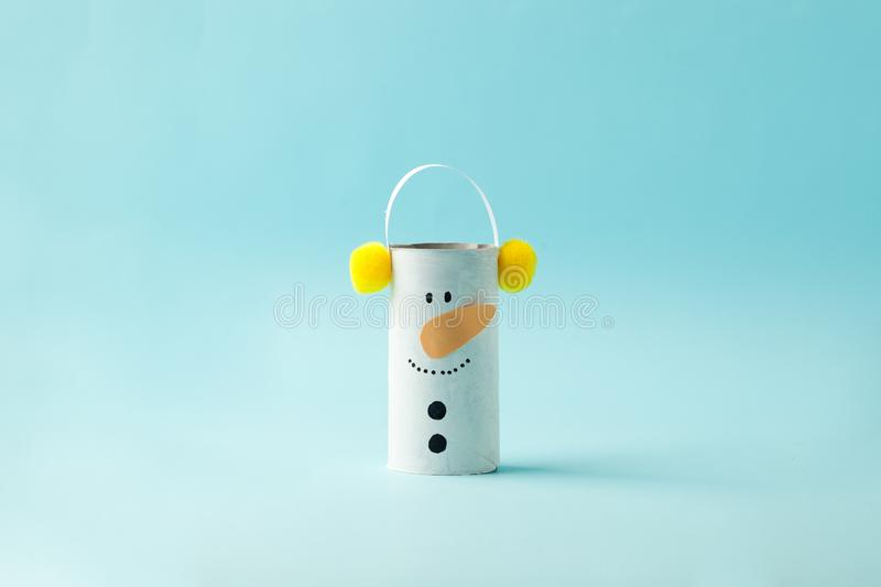 Paper Snowman for Happy new year Merry Christmas party. Easy craft for kids on blue background, simple diy idea from toilet rool. Tube, recycle concept, copy royalty free stock photo