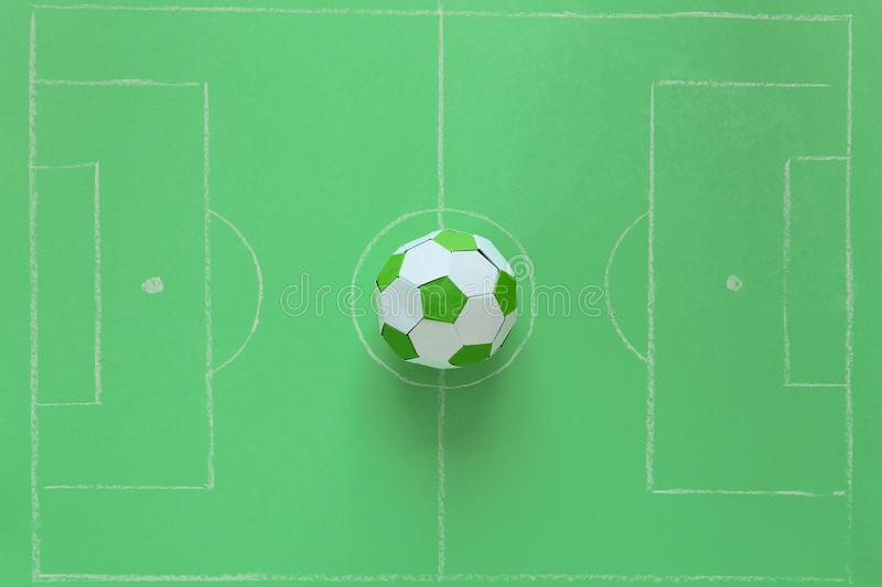 Paper soccer ball on soccer field or green background. Origami. Paper craft. Soccer game concept.  royalty free stock images