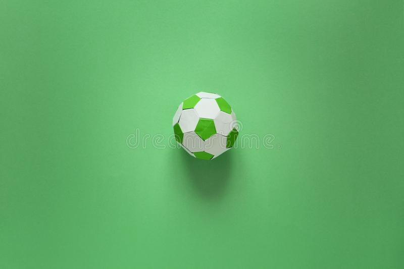Paper soccer ball on soccer field or green background. Origami. Paper craft. Soccer game concept.  stock images