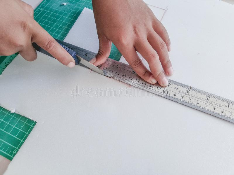 The child hand is cutting the foam paper with a cutter knife stock photography