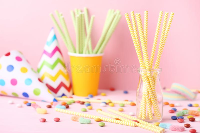 Paper straws with candies. On pink background royalty free stock photo