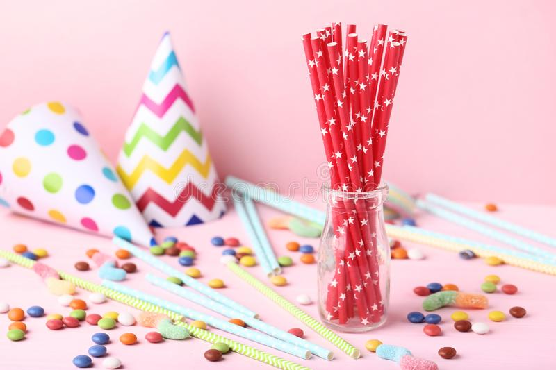 Paper straws in glass jar. With candies on pink background royalty free stock photography