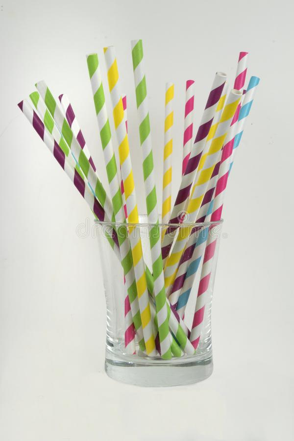 Paper straws in a glass. Multi colored paper straws in a short glass in a vertical format stock photos