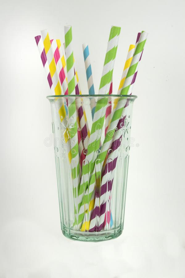 Paper straws in a glass. Multi colored paper straws in a tall glass in a vertical format royalty free stock photos