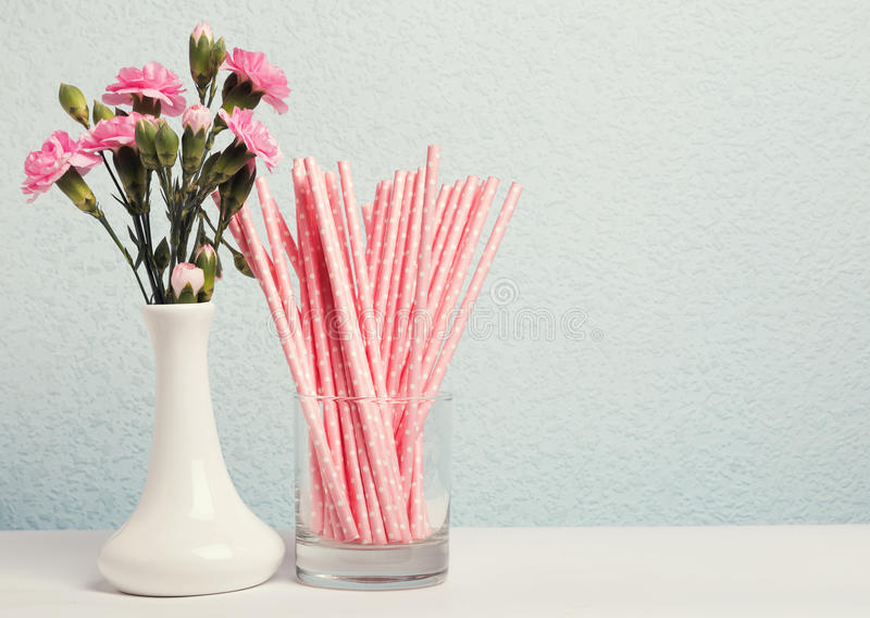 Paper straws and pink flowers royalty free stock photos