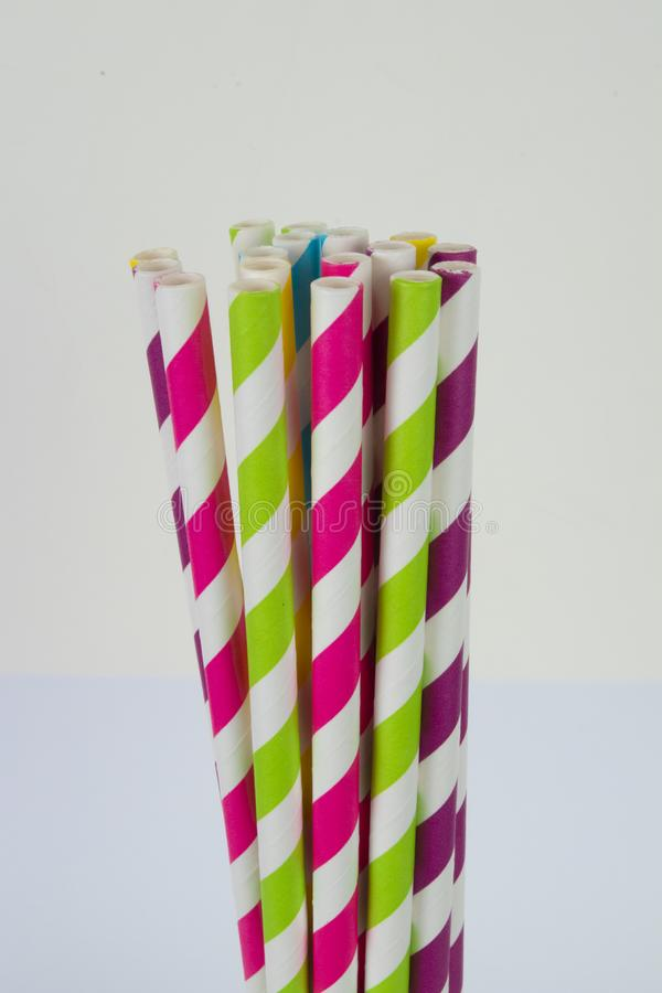 Paper straws in a vertical format on a white background. Multi-colored striped paper straws and ends in a vertical format against a white background stock photos