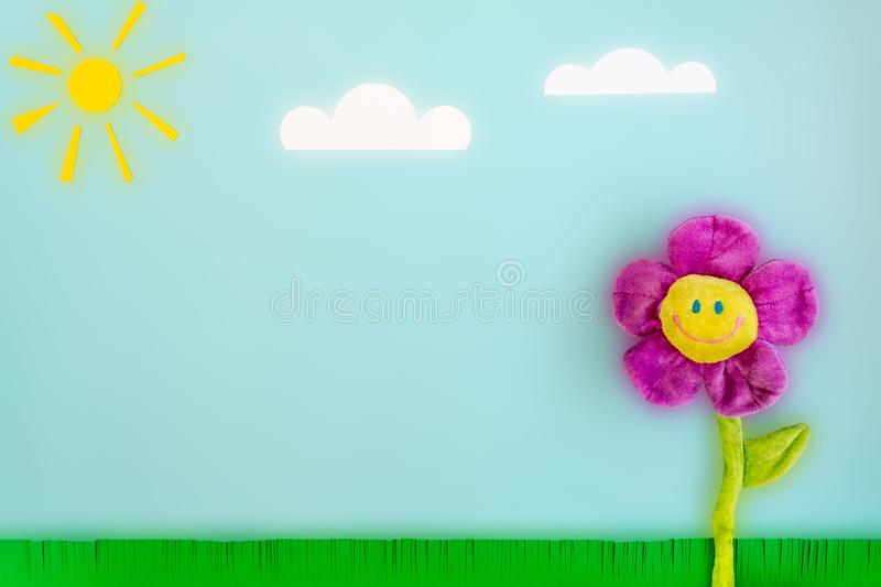 Paper sun, clouds, green grass and toy big flower with a smiling face on a blue background. stock photography