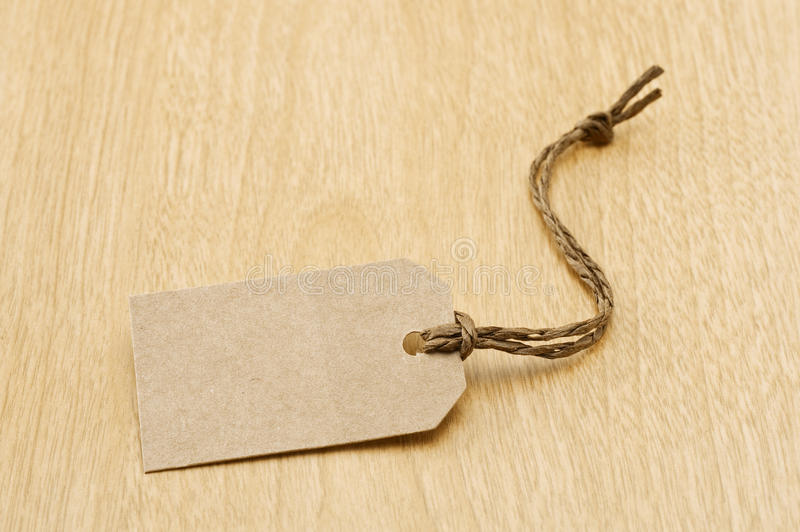 Paper tag. Blank brown paper tag on wooden table royalty free stock photo