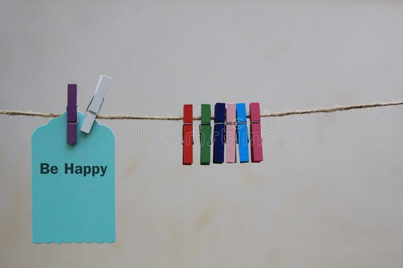 A paper tag `be happy` be positive concept background. A paper tag `be happy` to be positive and to live happily concept background stock photos