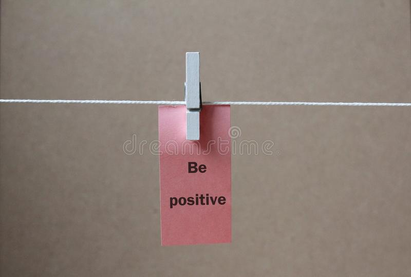 A paper tag `be positive` be positive concept background. A paper tag of `be positive` to be positive and to live happily concept background royalty free stock photography