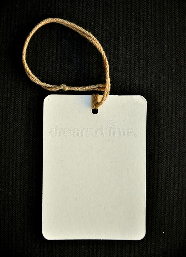 Paper tag on a black background. White paper tag on a black background. copy space for your text stock image