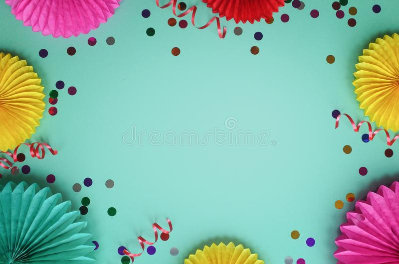 Paper texture color flowers with confetti on green background. Birthday, holiday or party background. Flat lay style. royalty free stock images