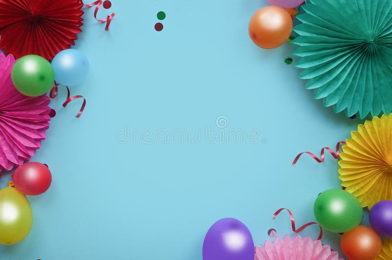 Paper texture flowers with confetti and baloons on blue background. Birthday, holiday or party background. Flat lay style stock photos