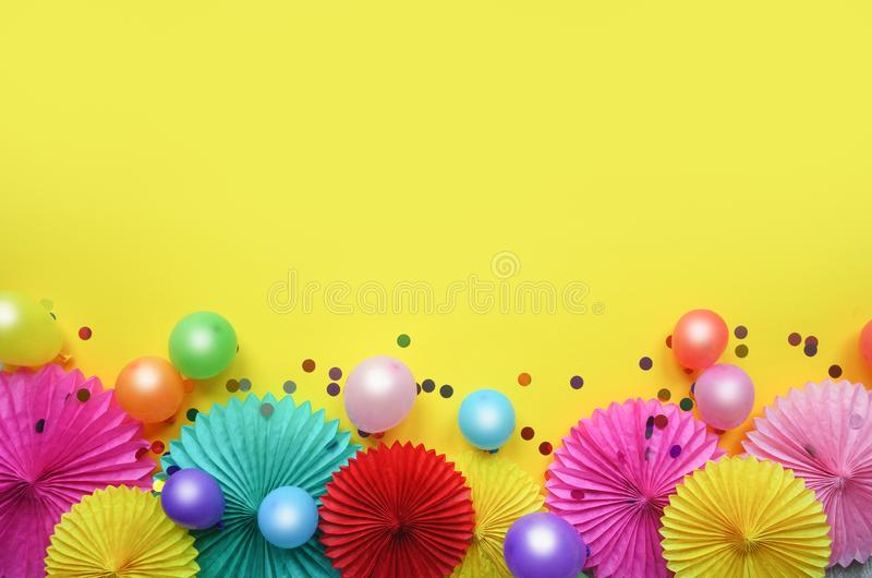 Paper texture flowers with confetti and baloons on yellow background. Birthday, holiday or party background. Flat lay style. royalty free stock photo