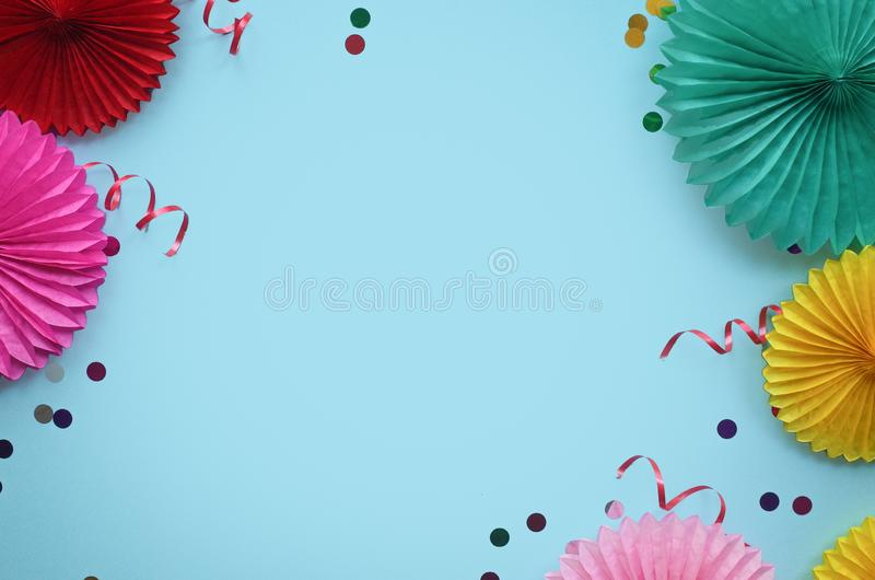 Paper texture flowers with confetti on blue background. Birthday, holiday or party background. Flat lay style stock photography