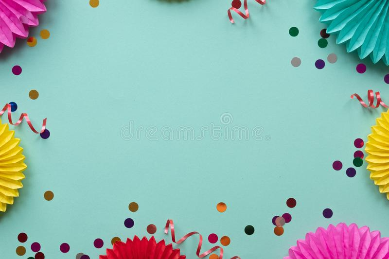 Paper texture flowers with confetti on green background. Birthday, holiday or party background. Flat lay style. stock images