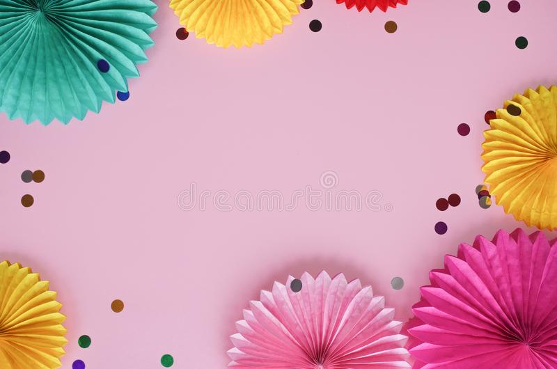 Paper texture flowers with confetti on pink background. Birthday, holiday or party background. Flat lay style. royalty free stock photo