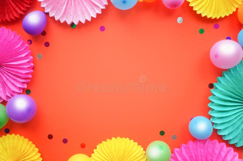 Paper texture flowers with different baloons on orang background. Birthday, holiday or party background. Flat lay style. Paper texture flowers with different stock photos