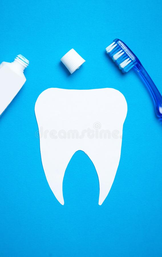 Paper Tooth with a toothbrush on blue background royalty free stock images