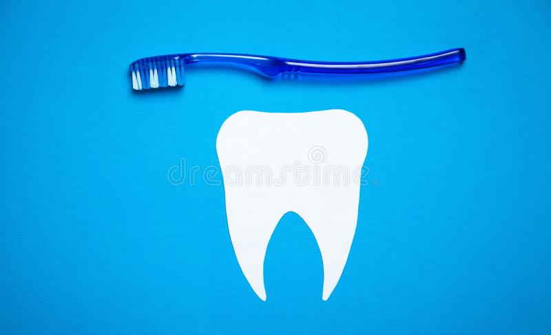 Paper Tooth with a toothbrush on blue background stock photo