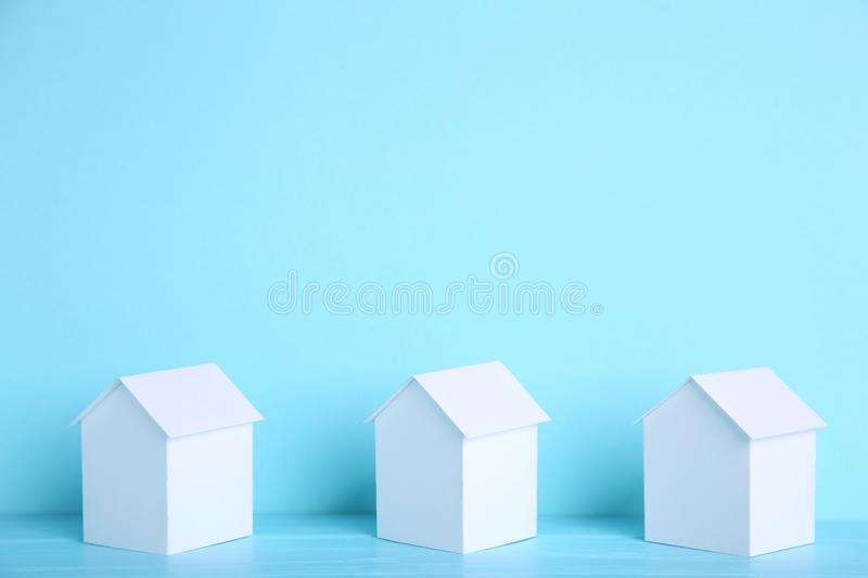 Blue paper house with coins isolated on white background royalty free stock image