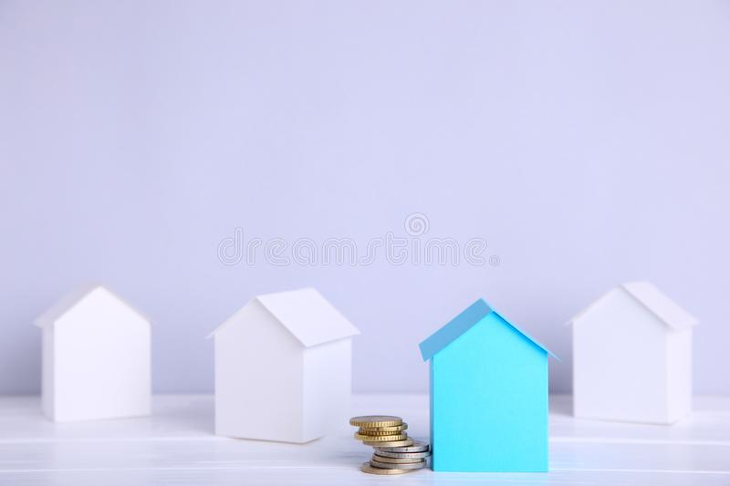 Blue paper house with coins on grey background stock images