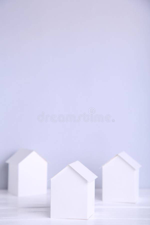 Blue paper house with coins on grey background royalty free stock photo